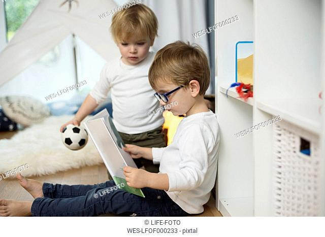 Two little boys playing at home, looking at picture book