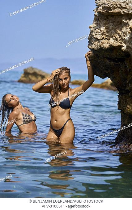 Greece, Crete, Chersonissos, women in bikini in sea, feeling sexy