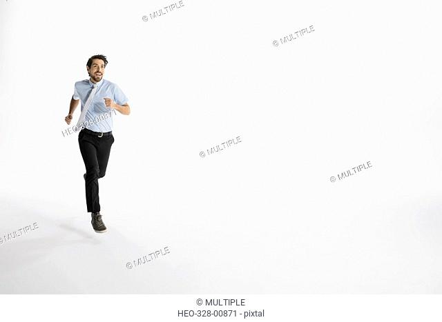 Enthusiastic businessman running against white background