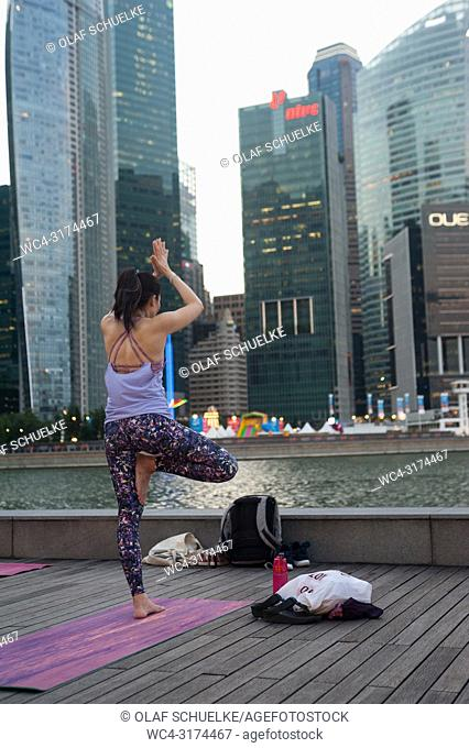 21. 12. 2017, Singapore, Republic of Singapore, Asia - A female participant of a yoga class is seen doing her yoga practise in Marina Bay with the skyline of...