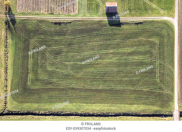 Green fields aerial view with hut and tracks