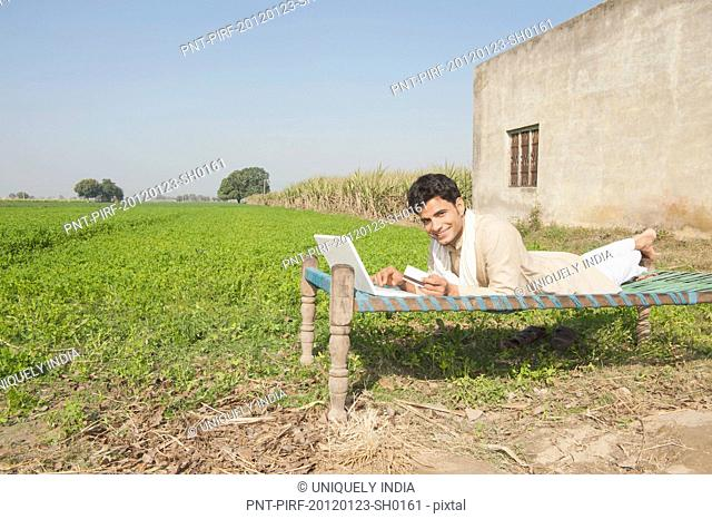 Farmer using a laptop and holding a credit card in the field, Sonipat, Haryana, India