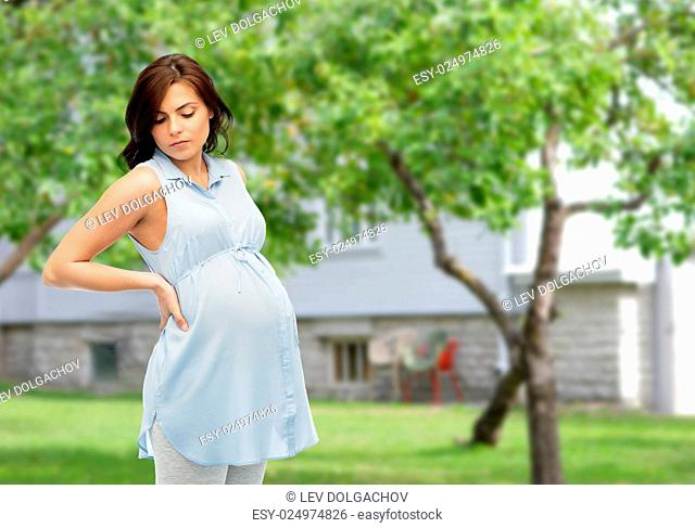 pregnancy, health, people and expectation concept - pregnant woman touching her back and suffering from backache over summer garden and house background