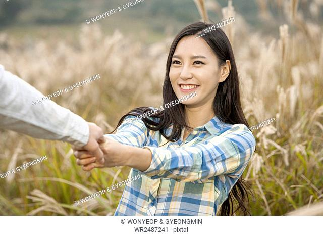 Portrait of young smiling woman pulling a hand against silver grasses