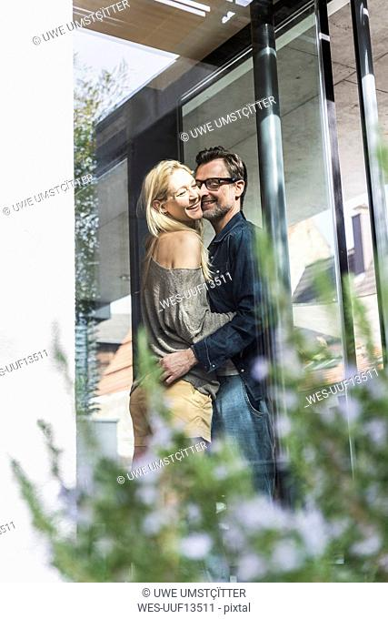 Happy mature couple standing on terrace of their house