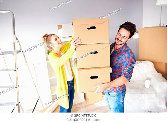 Young couple moving home, young man holding stack of cardboard boxes