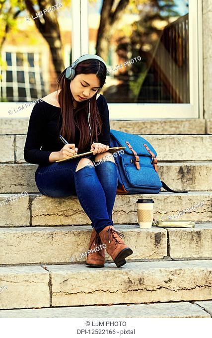 A young Chinese female university student sits on the steps listening to music using headphones and writes in notebook; Edmonton, Alberta, Canada