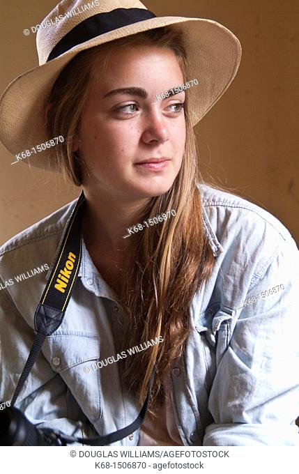 15 year old girl sits in an old abandoned house with her camera and wearing a Panama hat