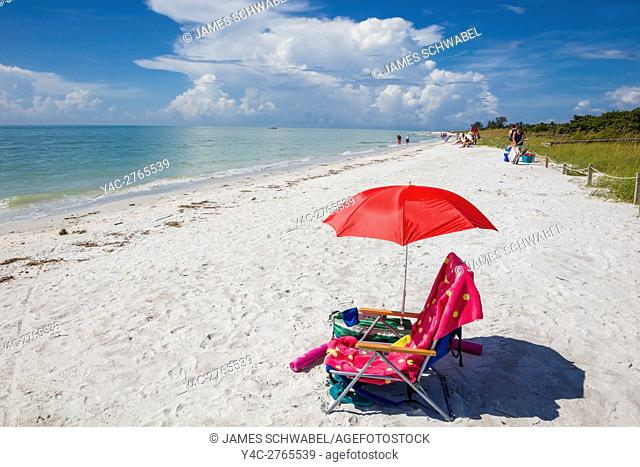 Red beach chair and umbella on Lighthouse Beach on Sanibel Island on the Gulf of Mexico Southwest Coast of Florida