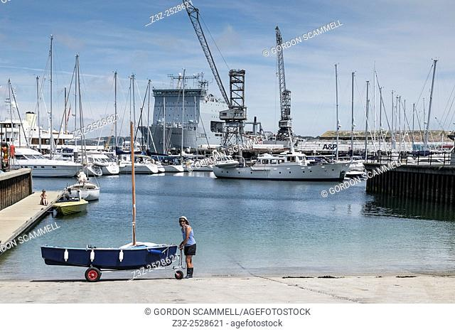 A woman about to launch a small sailing dinghy from a slipway in Falmouth, Cornwall