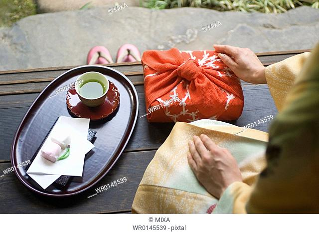 Young woman in kimono touching wrapped gift