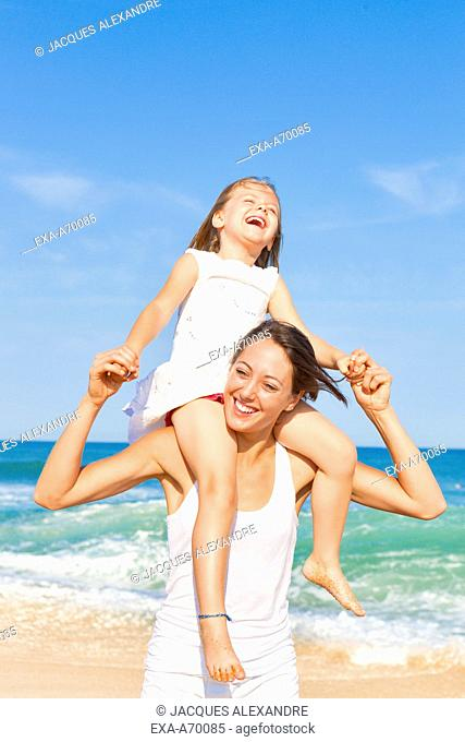 mother with daughter on shoulder at beach