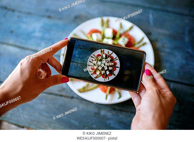 Hands of woman taking picture of food ready to eat, close-up