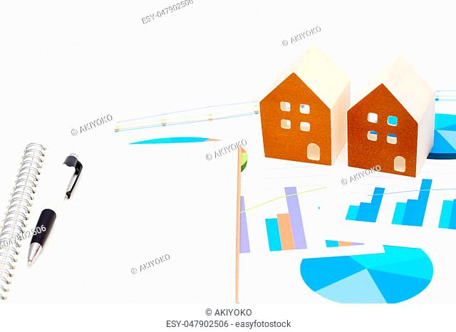 Miniature model of house on chart printed documents, notebook and pen