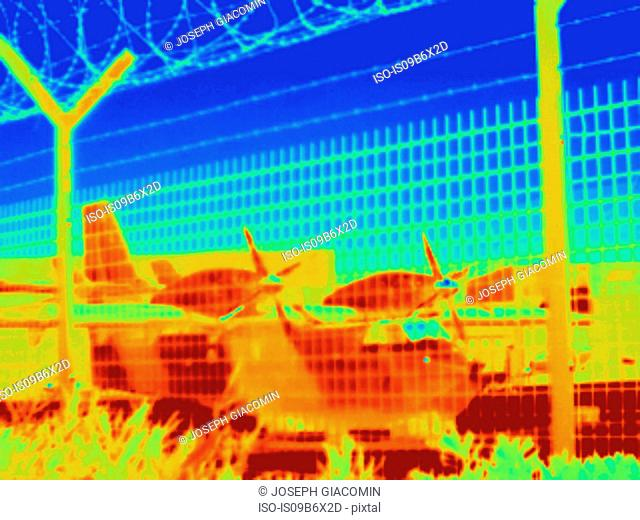 Thermal image of aeroplane seen through wire fence