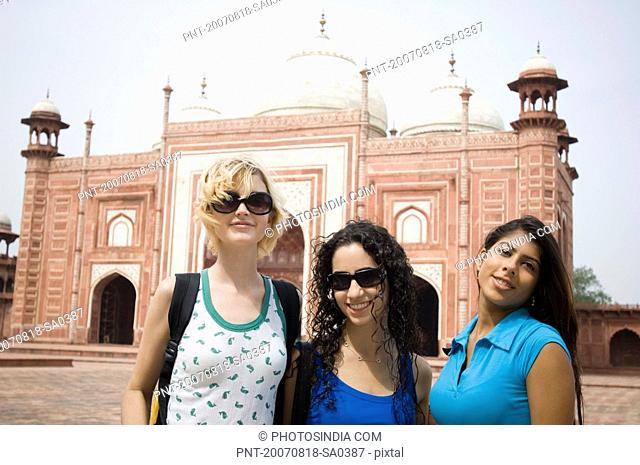 Portrait of three young women smiling in front of a mausoleum, Taj Mahal, Agra, Uttar Pradesh, India