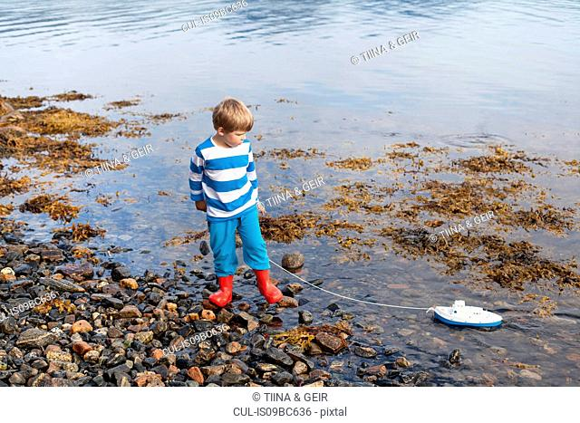 Boy at fjord water's edge playing with toy boat, Aure, More og Romsdal, Norway