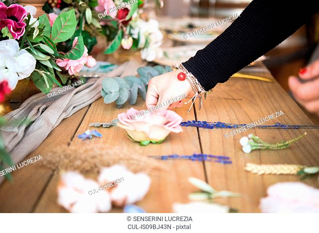 Woman arranging flower head and stems on wooden table, detail of hand