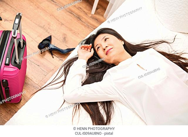 Business woman relaxing on bed in hotel room