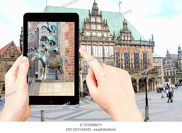 travel concept - tourist taking photo of Bremen Town Musicians statue on mobile gadget, Germany