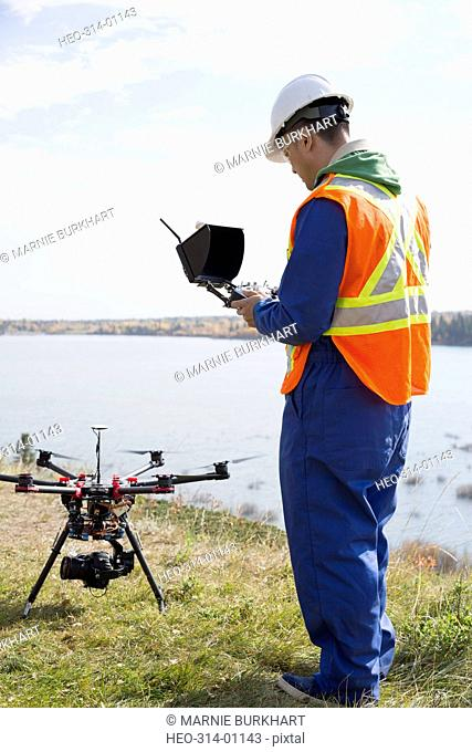 Surveyor with drone equipment at sunny lakeside