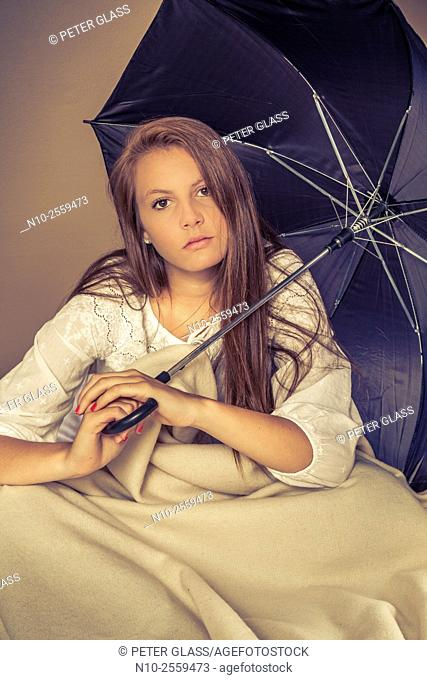 Teenage girl on her bed holding a black umbrella