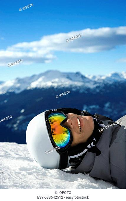 Caucasian teenage boy snowboarder wearing helmet and goggles, smiling, looking at viewer, lying in snow on mountain with mountain landscape in background