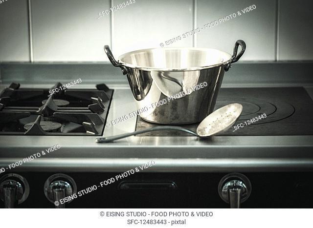 An aluminium pot and a draining spoon on a hob