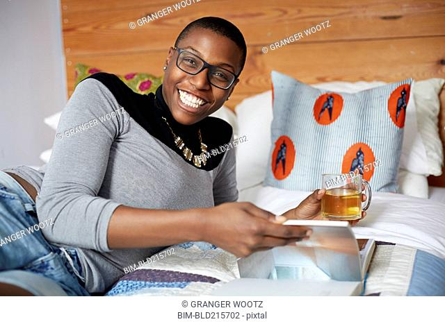Mixed race woman drinking tea and reading on bed