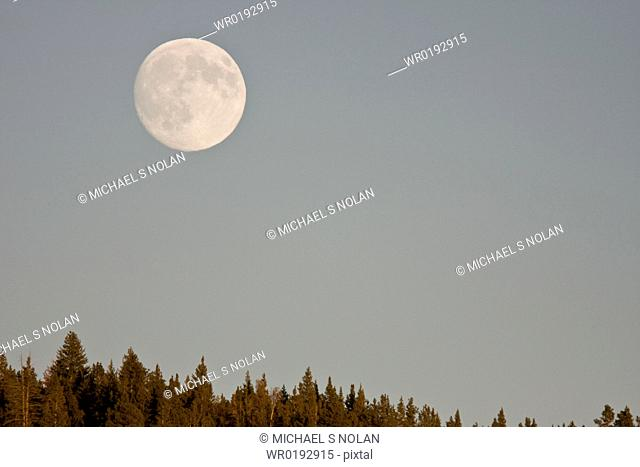 A full moon rising over the Haden Valley in Yellowstone National Park in the late fall