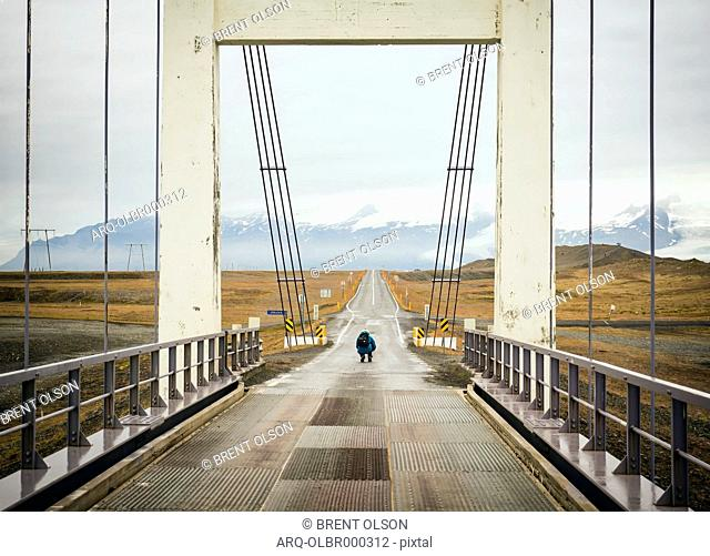 A Man Stops In The Middle Of A Bridge To Take A Picture