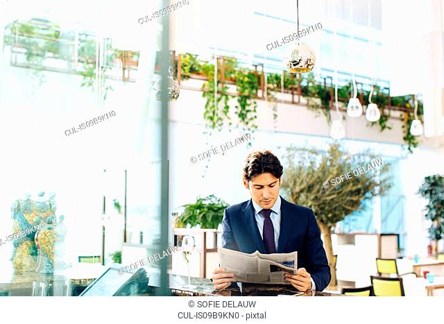 Businessman reading the newspapers while having drink at bar