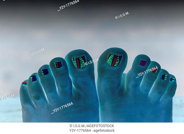 Feet in blue with decorated nails
