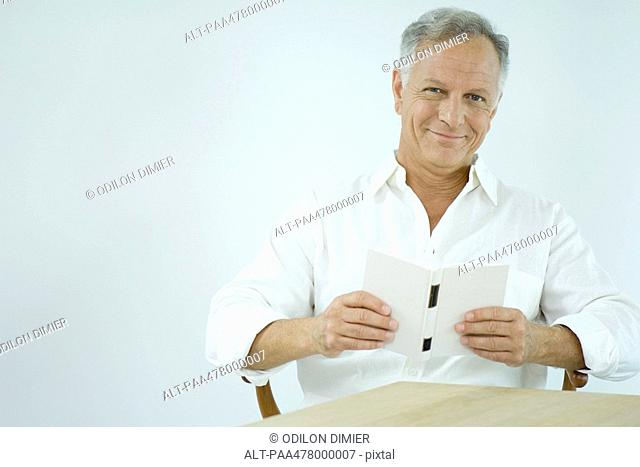 Mature man reading book, smiling at camera