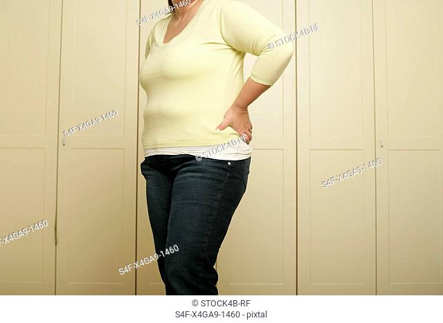 Overweight woman is standing in front of a wardrobe part of, close-up