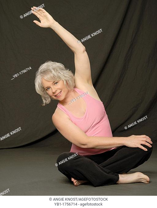 Attractive woman in her early 50s, stretching to warm up, wearing exercise clothes