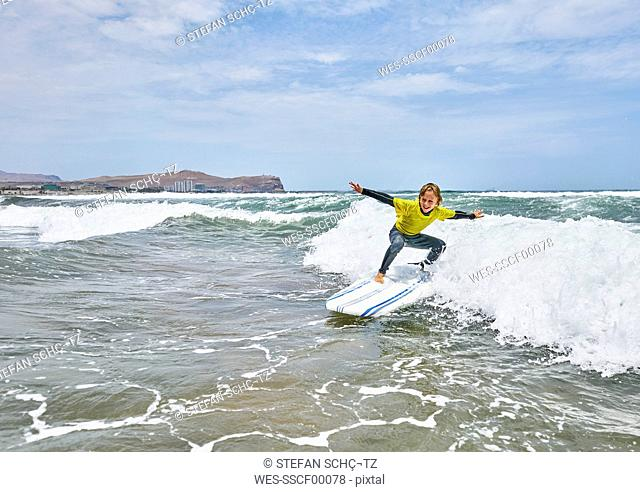 Chile, Arica, boy surfing in the sea