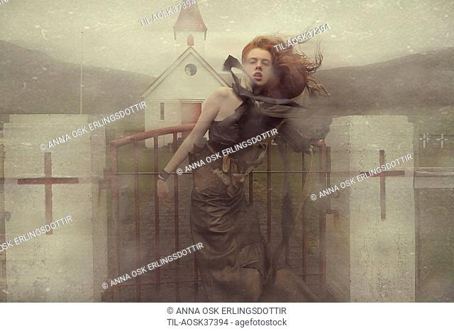 Lone female figure with red hair by church
