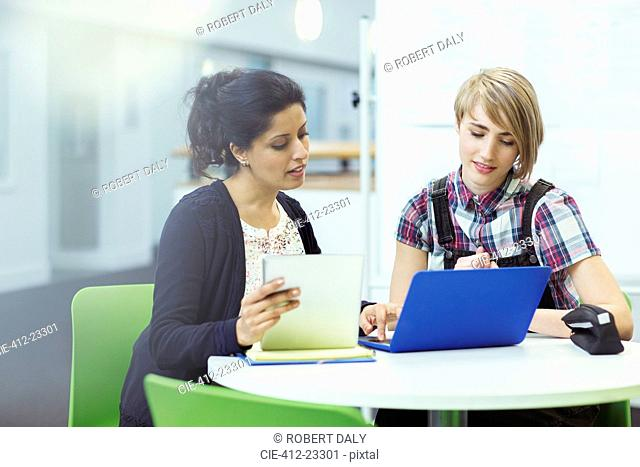 Teacher and student sitting together with digital tablet and laptop