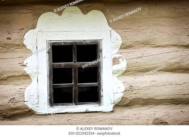 Window of ancient Ukrainian hut. Clay covered wall