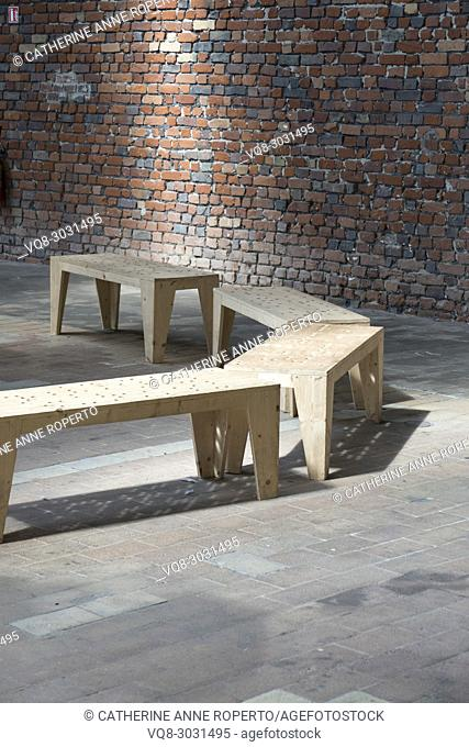 Semi circle of contemporary rectangular benches lit from above on rectangular floor tiles before a wall of rectangular terracotta and grey brick