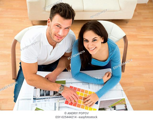High Angle View Of Young Couple Choosing Color From Swatch