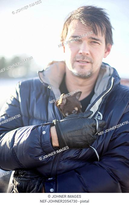 Man holding small dog under his jacket