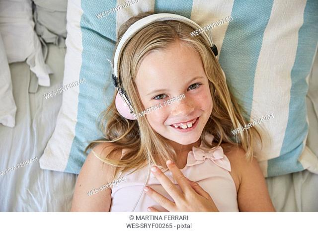 Portrait of smiling little girl lying on bed at home listening music with headphones