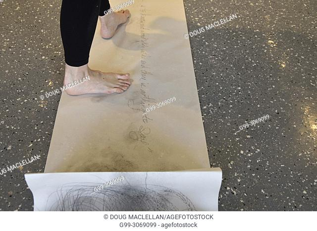 A rear view from the mid calf of a woman artist as she creates a performance art work at an artist run gallery in Windsor, Canada