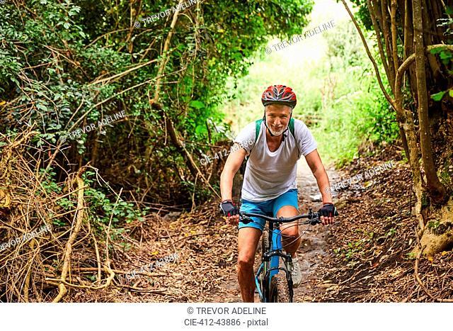 Mature man mountain biking on trail in woods