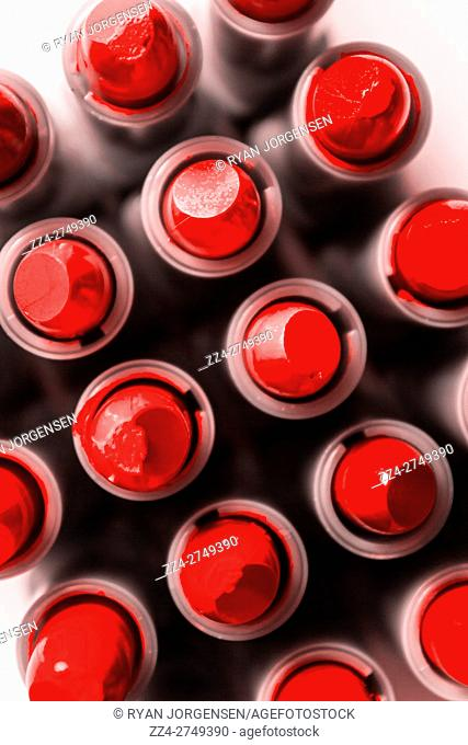 Numerous open tubes of red or scarlet lipstick densely packed together and viewed from overhead in a full frame beauty background