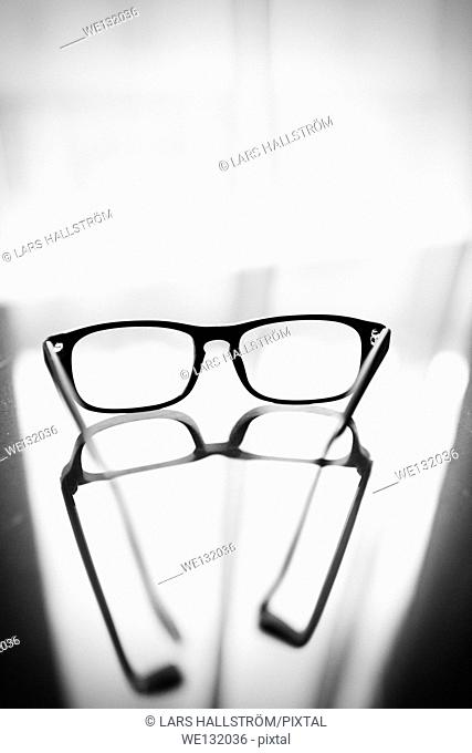 Eyeglasses on glass table in front of window with reflection of the glasses on the surface