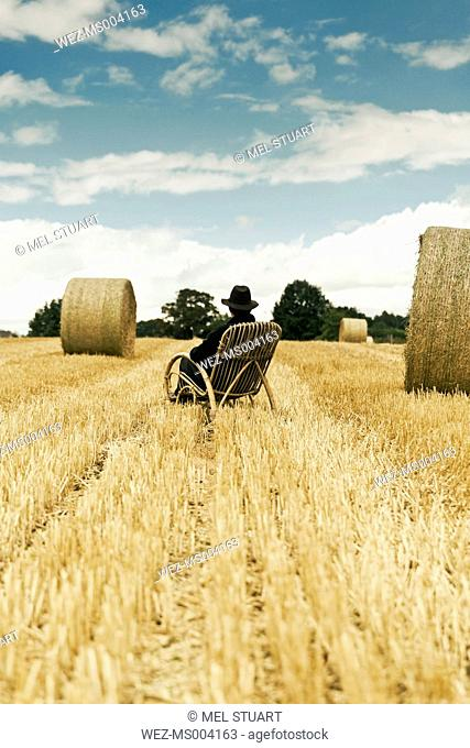 Teenage boy with hat sitting in a rocking chair on a grainfield