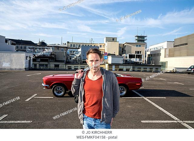 Portrait of mature man in front of his sports car on parking level